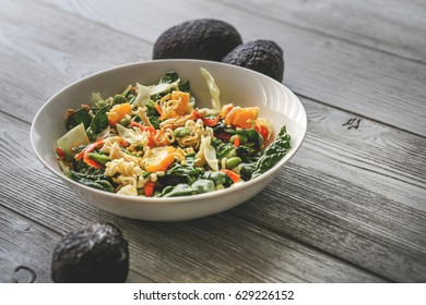 Asian Salad with mangoes, avocados, spinach, edamame beans, ramen, almonds, and carrots.