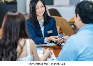 Asian Saleswoman recieving the credit card from couple customer when decision buy the new car after sign buy contract in showroom, credit card mockup