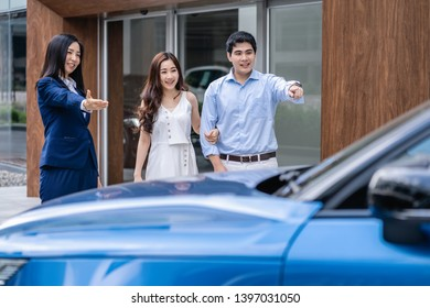 Asian Saleswoman welcoming the couple customer to checking the car infront of showroom,