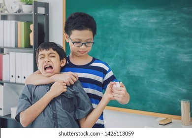 Asian school boy extort, bullying, weak friend on blackboard in classroom background with angry face.Bully and physical abuse of children and kid student concept.