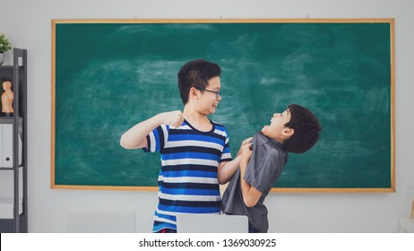 Asian school boy quarreling, punching, bullying, weak friend on blackboard in classroom background with angry face.Bully and physical abuse of children and kid student concept.