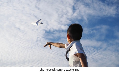 Asian school boy throwing a paper plane with blue sky background.(Selected focus)