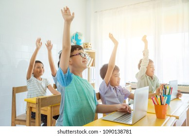 Asian school children rising hand up with smile in classroom