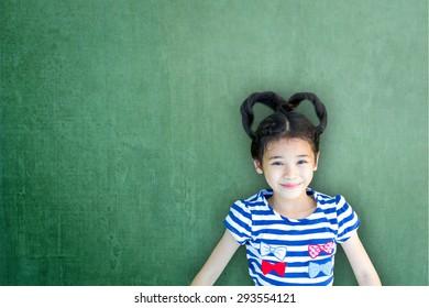 Asian school girl kid on green teacher class room chalkboard for educational concept