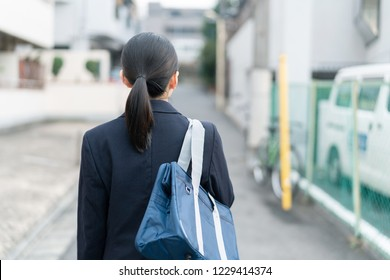 Asian school girl walking on the street.