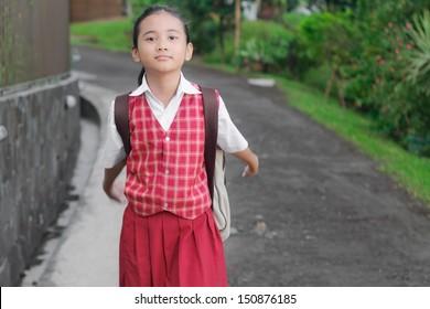 asian school girl walking on a asphalt pathway