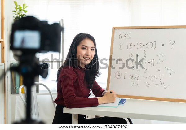 Asian school woman teacher working from home teaching online math subject to student studying from home. Girl using camera to record live on internet. Remote education class during covid19 pandemic.