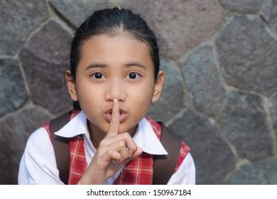 asian schoolgirl with finger on her lips