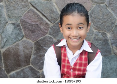 asian schoolgirl with ponytail shows a funny face