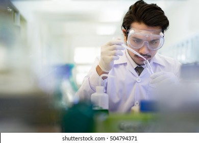 Asian scientist  in the laboratory working at lab with test tubes