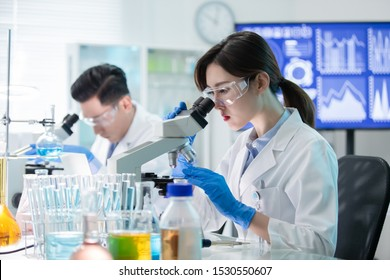 asian scientist team use microscope in the laboratory