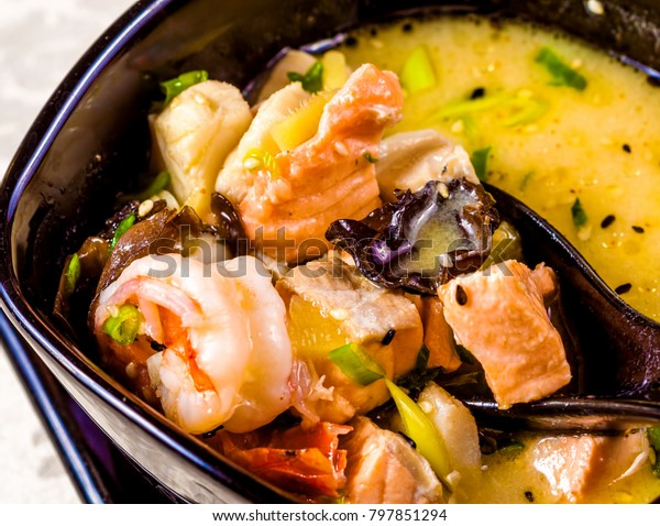 Asian seafood soup with spics and herbs in black bowl