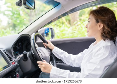 Asian senior age woman in a car