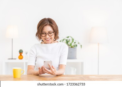 Asian senior age woman who uses smart phone