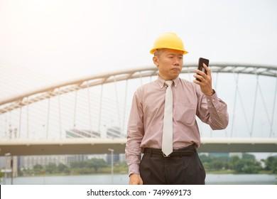 asian senior business architect using phone