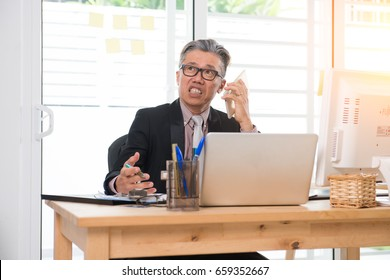 asian senior business male using the phone