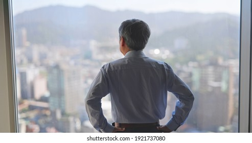 asian senior businessman is looking at city view through window