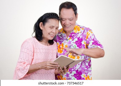 Asian Senior couple with book over white background