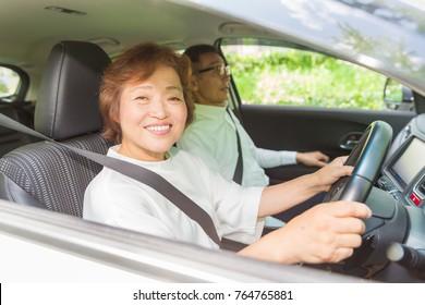 asian senior couple in a car