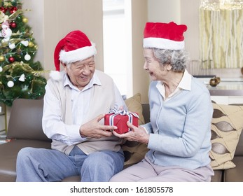 Asian senior couple with Christmas hats exchanging gifts.