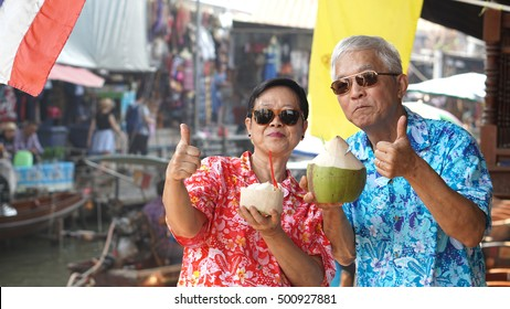 Asian senior couple drinking coconut juice at floating market. Travel to Thailand