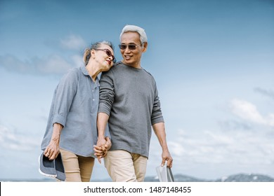 Asian senior couple or elderly people walking and siting at the beach on their weekend vacation holiday. Retirement vaction concept.