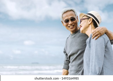 Asian senior couple or elderly people walking and siting at the beach on their weekend vacation holiday. Retirement vaction concept. Focus to a man.