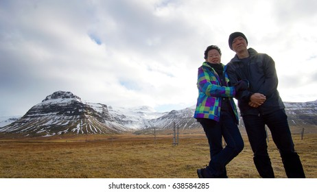 Asian senior couple enjoy anniversary trip in Europe. Iceland volcanic landscape mountain with snow view