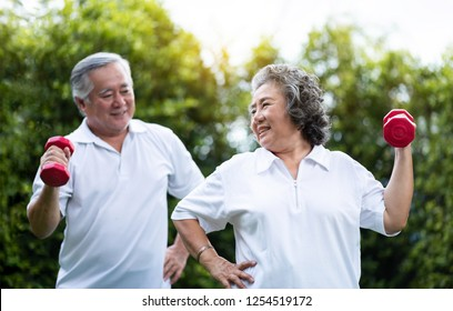 Asian Senior Couple exercising with red dumbbells at the outdoor park togetherness. Healthy, workout and relaxation in the morning concepts. Smiling Chinese or Thai or Japanese people.
