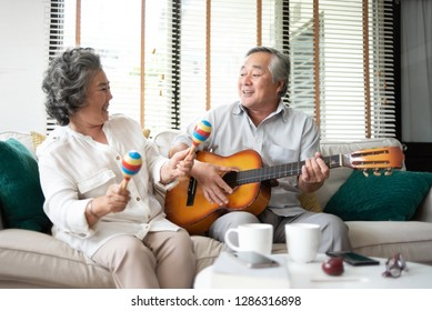 Asian senior Couple Having fun with singing and playing guitar together.