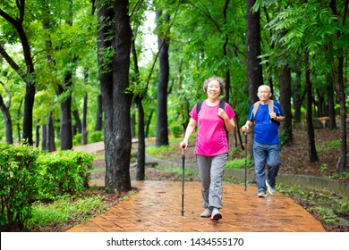 asian senior couple hiking on the forest park