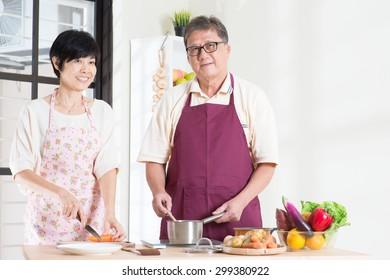 Asian senior couple preparing food at kitchen. Seniors living lifestyle at home.
