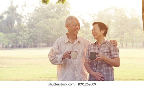 Asian senior couple relax drinking coffee in summer park, green background