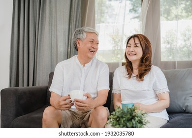 Asian senior couple relax at home. Asian Senior Chinese grandparents, husband and wife smile talking and drinking coffee while lying on sofa in living room at home concept.