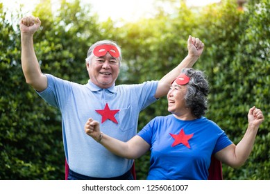 Asian Senior couple in Superhero costume relaxing and celebrating with victory. Elderly people wear red masks and blue shirt with stars having fun, smiling at the park outdoor togetherness.