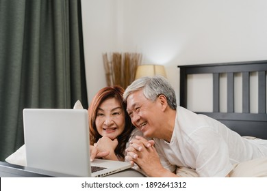 Asian senior couple using laptop at home. Asian Senior Chinese grandparents, husband and wife happy after wake up, watching movie lying on bed in bedroom at home in the morning concept.