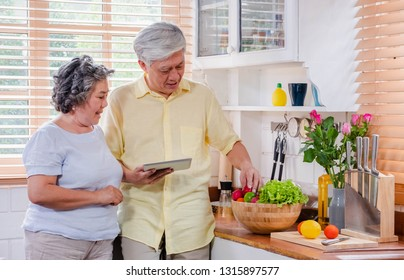 Asian senior couple using table computer to searching menu recipe and type of vegetable in kitchen at home.senior with technology lfiestyle.aging at home