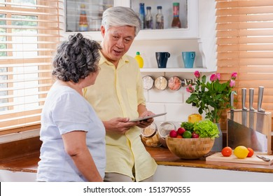 Asian senior couple using tablet computer to searching menu recipe and type of vegetable in kitchen at home.senior with technology lfiestyle.aging at home