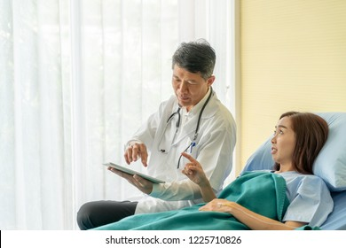 Asian senior doctor sitting on hospital bed and discussing with female patient - selective focus point