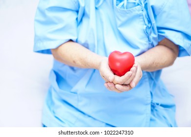 Asian senior or elderly old lady woman patient holding red heart in her hand on bed in nursing hospital : healthy medical concept