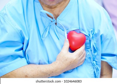 Asian senior or elderly old lady woman patient holding red heart in her hand on bed in nursing hospital : healthy strong medical concept