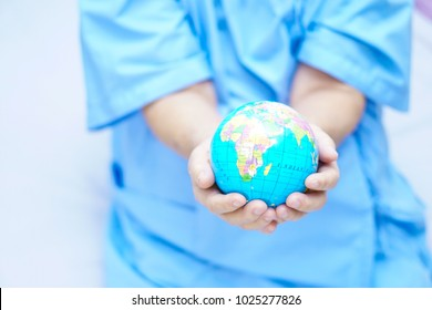 Asian senior or elderly old lady woman patient holding globe world in her hand on bed in nursing hospital : healthy strong medical concept