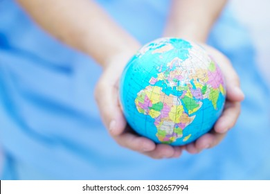 Asian senior or elderly old lady woman patient holding globe world model in her hand on bed in nursing hospital : healthy strong medical concept