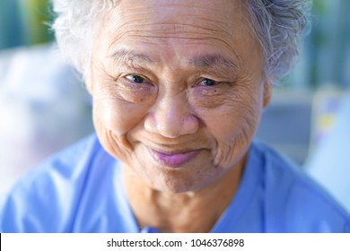 Asian senior or elderly old lady woman patient smile bright with strong health while sitting on bed in nursing hospital : healthy strong medical concept