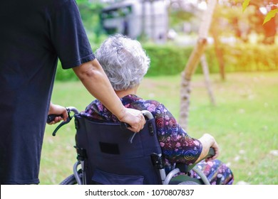Asian senior or elderly old lady woman patient sitting on wheelchair at park in holiday : healthy strong medical concept