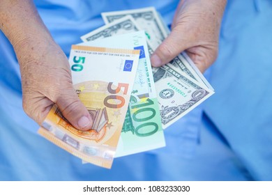 Asian senior or elderly old lady woman patient holding worry US dollar Euro banknotes money treatment fee payment while sitting on bed in nursing hospital ward : healthy strong medical concept