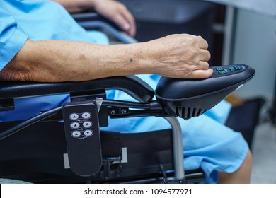 Asian senior or elderly old lady woman patient on electric wheelchair with remote control at nursing hospital ward : healthy strong medical concept