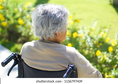 Asian senior or elderly old lady woman sitting on wheelchair with strong health at park in happy holiday