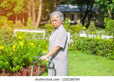Asian senior or elderly old lady woman patient walk with walker in park with happy : healthy strong medical concept