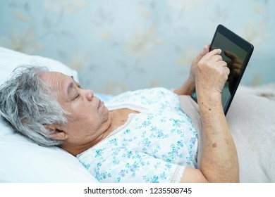 Asian senior or elderly old lady woman patient holding in her hands digital tablet and reading emails while sitting on bed in nursing hospital ward : healthy strong medical concept